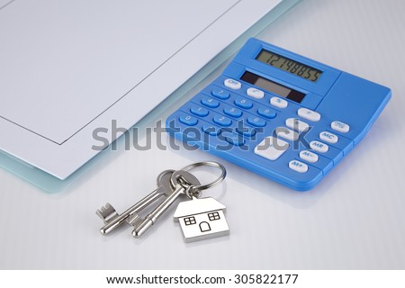 House shaped key chain with keys and calculator - stock photo