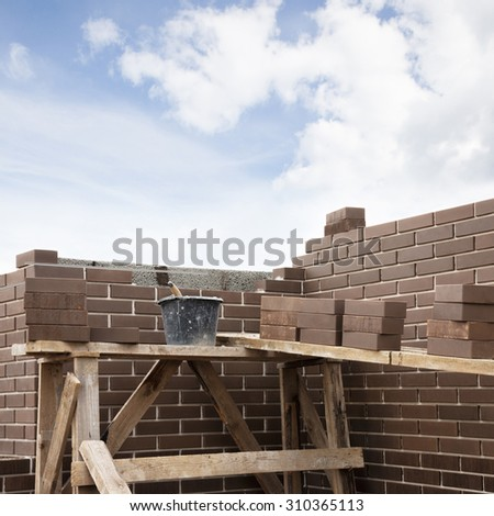 House under construction. Bucket with masonry cement and brown clinker bricks at scaffolding boards. Space for text. - stock photo