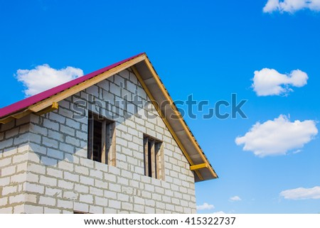 house under construction from aerated concrete blocks. unfinished house with a red roof against the blue sky and clouds. copy space for your text - stock photo