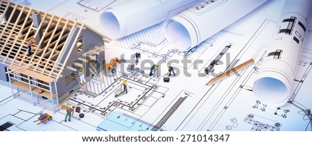 house under construction on blueprints - building project - stock photo