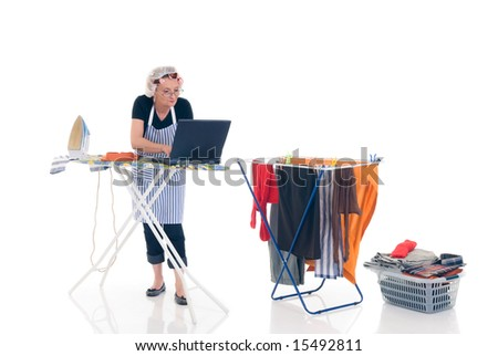 House wife, basket with ironed goods, clothes line with washed clothing, daily household, chatting on laptop. - stock photo