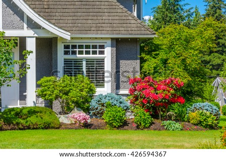 House window with nicely trimmed and landscaped front yard, lawn. - stock photo