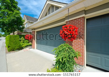 House with double doors garage and hanging buckets with flowers in the suburbs of Vancouver, Canada. - stock photo