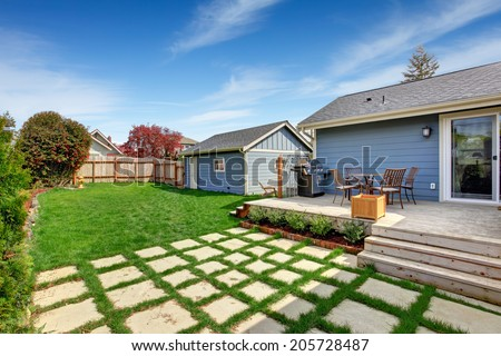 House with fenced backyard. View of wooden walkout deck with small patio area - stock photo