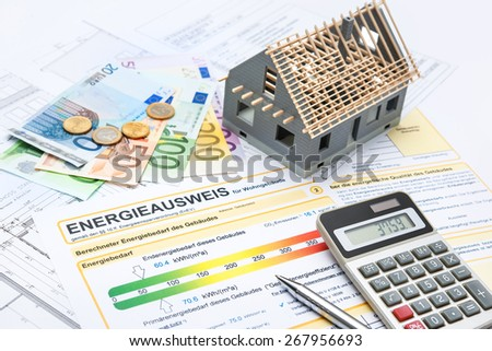 House with money, calculator and an energy efficiency certificate - stock photo