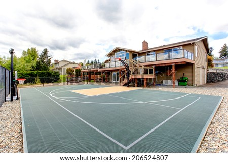 House with sport court and patio area. View of green court - stock photo
