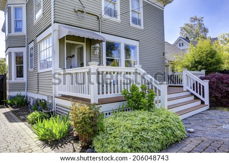 House with walkout deck. View of flower bed and brick tile walkway - stock photo