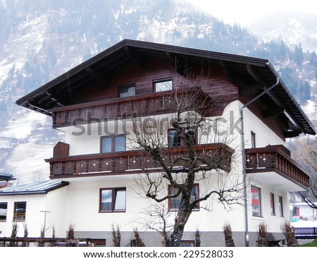 House with wooden balcony in winter mountain village, Austria - stock photo