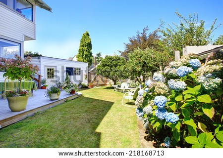 House with wooden patio decorated with flower pots and garden with sitting area and apple trees - stock photo