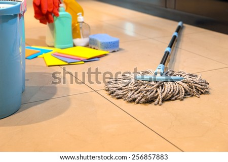 Household string mop and bucket for cleaning the floors with various cleaning supplies in the background - stock photo