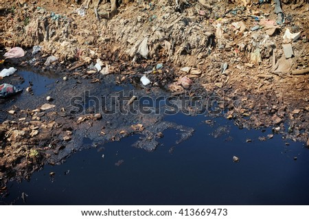 Household trash and toxic industrial garbage contaminates a river and soil at Bali's largest and most polluted landfill site in Suwung, Bali, Indonesia. - stock photo