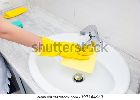 Housekeeper or housewife cleaning a white tiled bathroom wiping off the hand basin and tap with a yellow cloth, closeup of her hand - stock photo