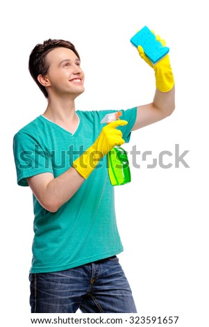 Housekeeping concept. Studio portrait of handsome young man in gloves cleaning glass with wisp and sprayer. Isolated on white. - stock photo