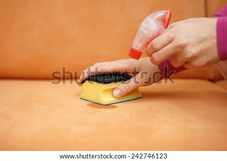 housemaid is cleaning stain on sofa with spray bottle and sponge - stock photo