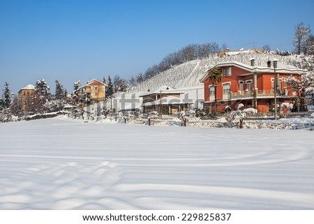 Houses and rural field covered with snow in Piedmont, Northern Italy. - stock photo