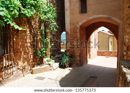 Houses behind an arc in historical ocher village of Roussillon, Provence, France - stock photo