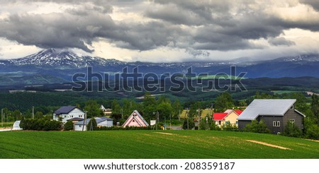 Houses in grass field with mountain ranges background, Hokkaido, Japan - stock photo
