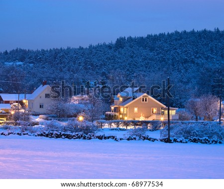 Houses in snowy landscape during sunset - stock photo