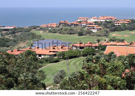 Houses line a golf course at an upmarket seaside housing estate. - stock photo