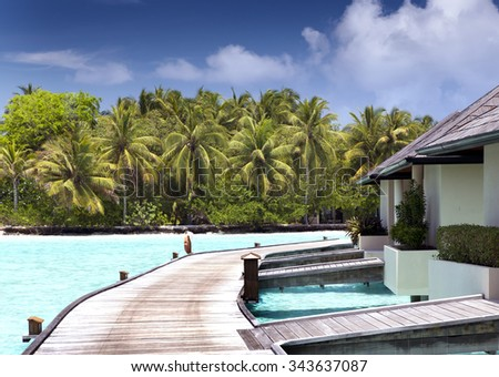 houses over the transparent quiet sea water  and a palm tree - stock photo