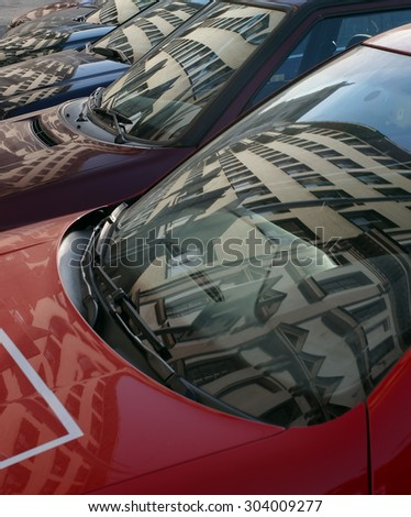 Houses reflected in a cars windshields. Parking next few passenger cars. Abstract photo, in front of the vehicles its in front windscreens, bonnets and wipers. A lot of cars in the parking. - stock photo