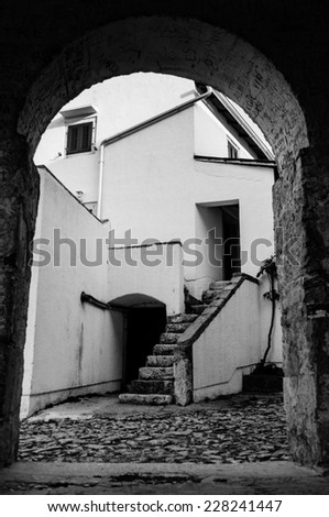Houses through arcad at Beli in Cres island - Croatia BW - stock photo