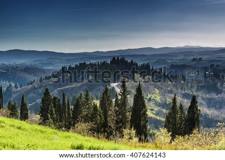 Houses with cypress trees in a green spring day. - stock photo