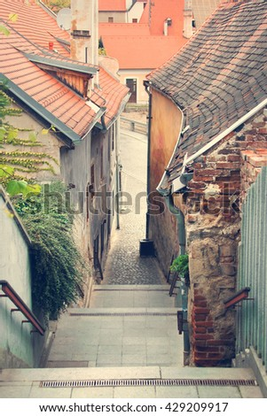 Houses with red tile roofs and stairs leading down in a beautiful old city - stock photo