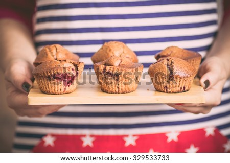 Housewife brings a plate with chocolate muffins - stock photo