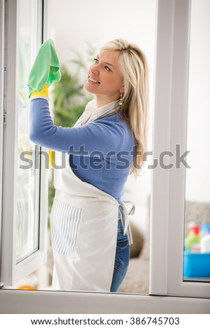 Housewife clean window glass and make spring cleaning - stock photo