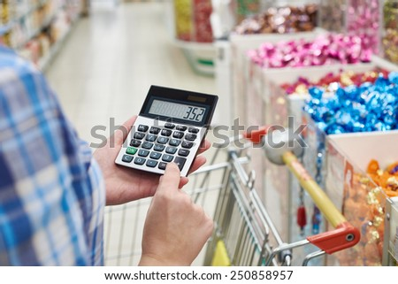 Housewife considers costs in the store - stock photo