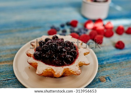 Housewife cook delicious tarts of shortcrust pastry filling derived from fresh blueberry syrup - stock photo