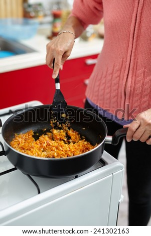 Housewife cooking stir fry vegetables in a pan on a stove - stock photo