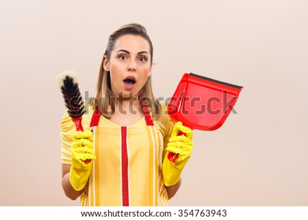 Housewife has got a lot of things to clean,she is in panic and she is wondering will this chores ever end.Housewife in panic - stock photo
