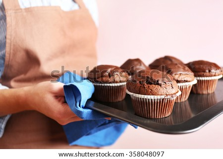 Housewife holding oven-tray with chocolate cupcakes, close up - stock photo