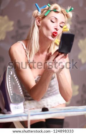 Housewife irons clothes and makeup corrects - stock photo