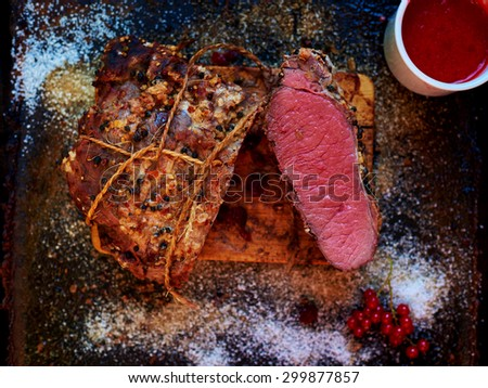 Housewife pulled out of the oven, a large piece of pork, which she cooked in a pan, a good pre-season it with spices and herbs - stock photo