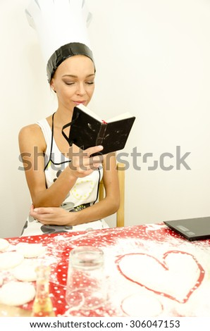 Housewife reads the recipe for the dough - stock photo