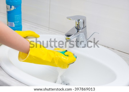 Housewife rinsing off a sponge for cleaning the bathroom under the running water from the hand basin, close up view of her gloved hands - stock photo