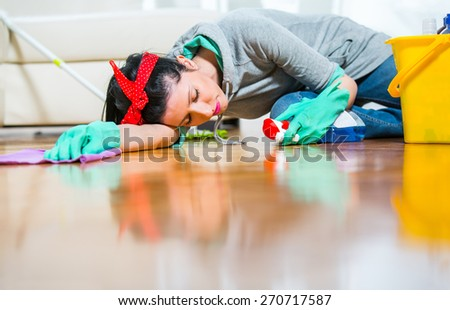 Housewife tired of cleaning sleeping on the floor - stock photo
