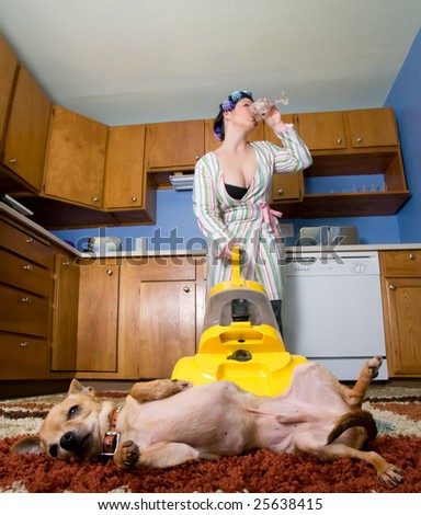 housewife vacuuming while drinking alcohol - Domestic series - stock photo