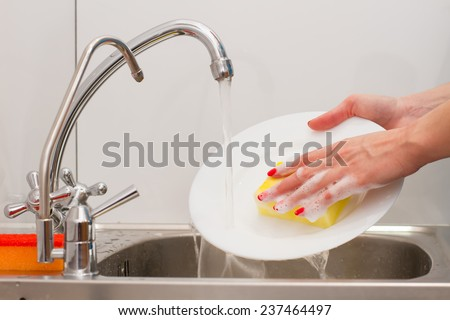 housewife with  nice manicure washes dishes - stock photo