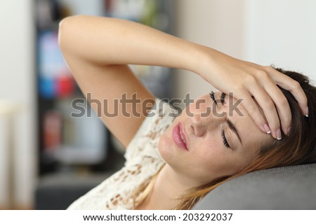 Housewife woman in a couch with headache and a hand on forehead - stock photo