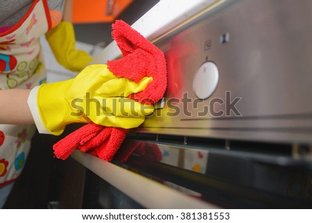 housework and housekeeping concept - close up of woman hand in yellow gloves cleaning oven. copy space - stock photo