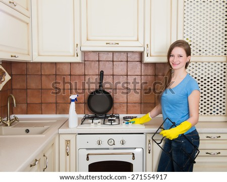 Housework and housekeeping concept - happy young woman with bottle of spray cleanser cleaning oven at home kitchen. - stock photo
