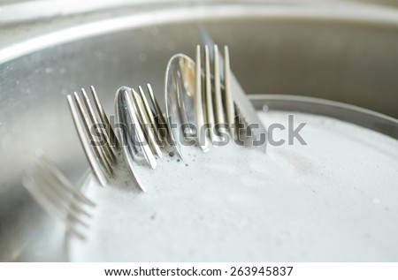 housework, washing-up and housekeeping concept - close up of dirty dishes washing in kitchen sink - stock photo