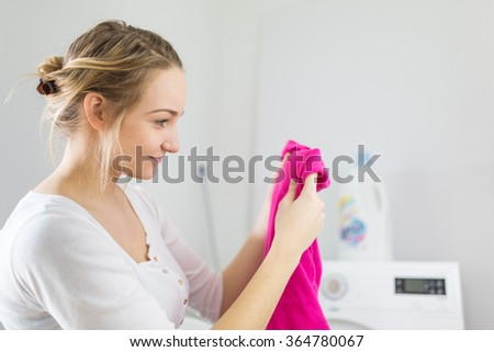 Housework: young woman doing laundry - putting colorful garments into the washing machine (shallow DOF; color toned image) - stock photo