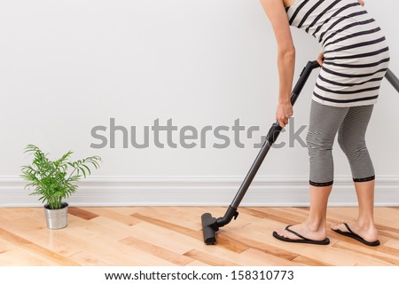 Housework. Young woman vacuum cleaning the apartment. - stock photo