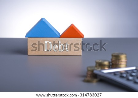 Housing Loan concept. House Wooden Block, coins and calculator with word Debt  - stock photo