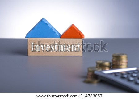 Housing Loan concept. House Wooden Block, coins and calculator with word Investment  - stock photo